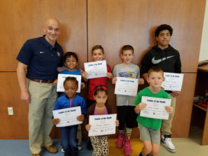 Students of the Month holding their certificates with the principal