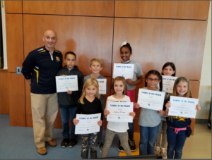 Principal stands with the students of the month holding their certificates.