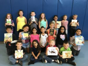 Class posing with donated books